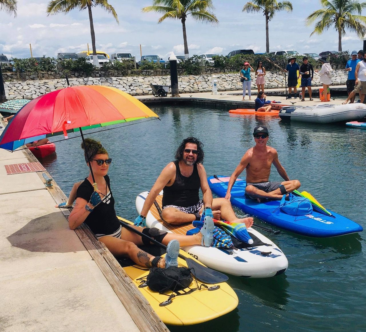 Three people sitting on a row of paddleboards floating in water. They are wearing sunglasses and smiling at the camera. One person is holding a rainbow colors umbrella.