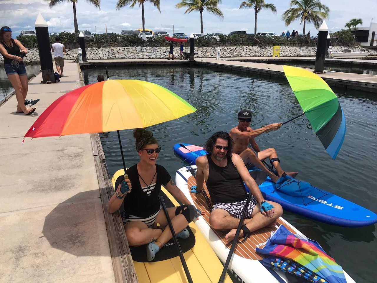 Three smiling people on paddleboards at a dock, side by side. Two of them are holding rainbow-themed umbreallas.
