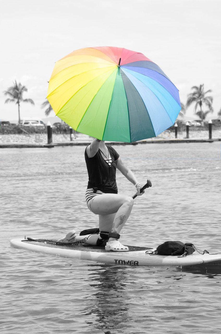 Dahlia on a paddleboard in a lunge position holding an umbrella high. All of the image is in black and white except the rainbow umbrella. .  u